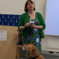 Lynn Cox, in a patterned dress and green cardigan, leads a Workshop Session.  Her golden labrador looks up at her.