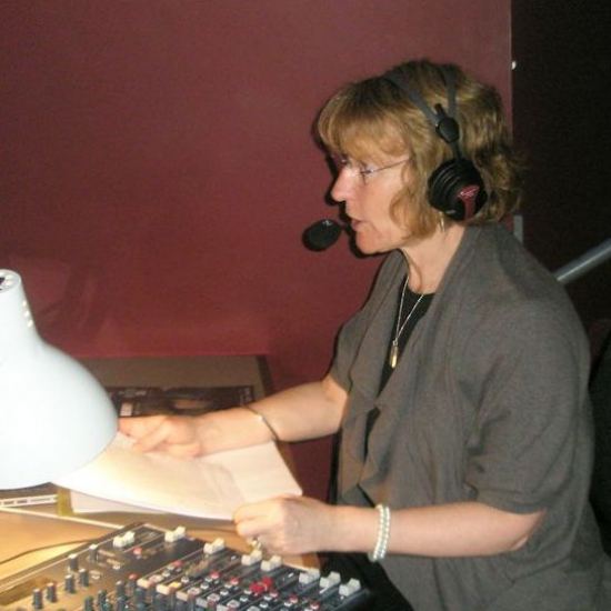 A woman is reading a script and talking into a microphone, large headphones cover her ears.. A large white lamp and other equpment are on her desk..